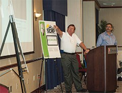 """Energy managers were also asked to make 5-minute """"Pechu Kucha"""" presentations, which is a format for delivering short, concise messages. In this case, energy managers were asked to speak about the projects they were undertaking in their districts.  At left, Larry Curry and David Rorrer, co-energy managers in Madison County Schools make their presentation."""