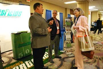 Owensboro Independent school board member Cate Lauzon talked to Vescio's Sportsfields representatives Chris Parks, left, and Bucky Trotter in the exhibitors area.