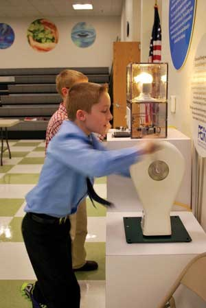 Fourth-grader Lincoln Mattox uses his arms to spin a generator attached to LCD, traditional incandescent and LED light bulbs. It demonstrates how much energy it takes to power each type of bulb. The experiment was created by students at the University of Kentucky.