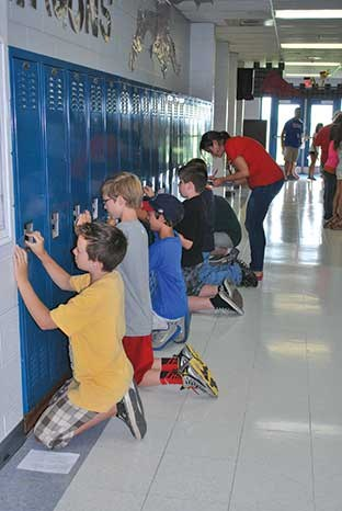 This group of students concentrated intently while learning how to work the combination locks on their new lockers, with the help of teachers.