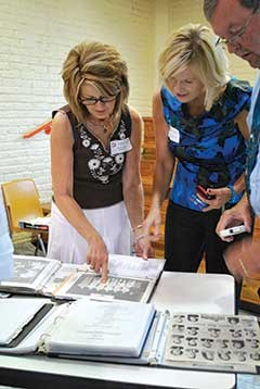 Sisters Donna Whitehead and Jeana Whitehead Crouch find a picture of their father in binders with pictures of the school's graduating classes. At right is James Crouch.