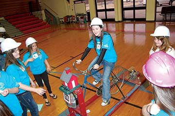 "Sixth-grader Kathryn Arnold marks the delivery of the ""coal"" to the ""bucket"" by pedaling a bicycle attached to and powering a radio and a light."