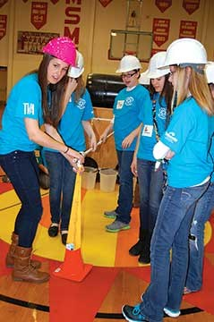 Members of the high school engineering program lead each team through the process. Junior Bree Tuohy, in the pink hard hat, helps her squad adjust an angle in the pipeline through a cone obstacle.
