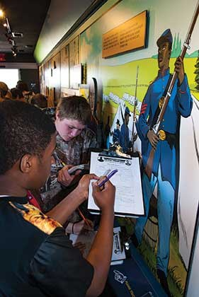 "Eighth-graders Brisean Corde (left) and Jacob Carpenter take notes on one of the exhibit's featured characters, Elijah Marrs, a slave who chose to join the Union Army. Others covered in the exhibit include Senators Henry Clay and John J. Crittenden, Supreme Court Justice John Marshall Harlan and Ellen Wallace, a ""slave-owning woman trying to adjust in a changing world."""