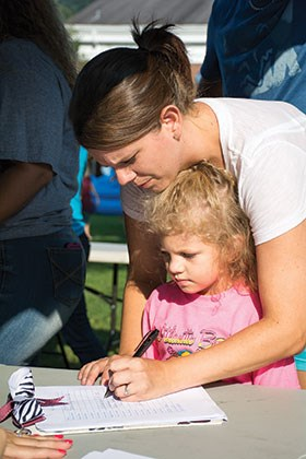 Kristen Carnes gets daughter Haleigh Brooke signed up for kindergarten at one of the information tables for each school. Nearby at the high school table, members of the Class of 2015 compared notes about their final class assignments.