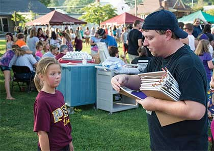 Josh Richardson of Mountain Comprehensive Health Corporation hands fourth-grader Halle Jones some school supplies. Local vendors joined youth and family services providers with family support information.