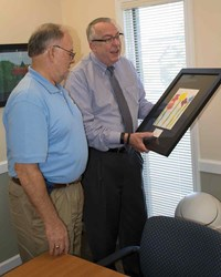 "Armstrong (right) and KSBA President Allen Kennedy of Hancock County examine one of the prints in the room where the KSBA Board of Directors conducts many of its quarterly meetings. Armstrong said, ""The opportunity to display the unique student art will allow our guests to view their work and hopefully support expanding the VSA program."""