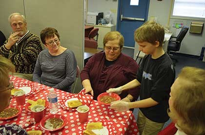 Fourth-grader Jason Hodges serves taco soup to, from left, Ashland school board member Charlie Chatfield, district support Jessie Singleton, student services director Lisa Henson and district consultant Janice Ledford.