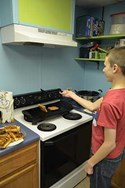 Sixth-grader Chris Evans prepares grilled cheese sandwiches, his specialty, for the group.