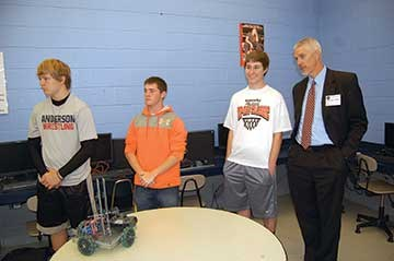 Anderson County Judge-Executive Orbrey Gritton stands with students during a presentation by the high school's robotics team. During the tour, visitors also witnessed a civil engineering design demonstration, a culinary class studying food nutrition and preparations for the annual plant sale at the school's greenhouse.