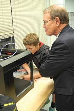 Lawrenceburg Mayor Sandy Goodlett watches as Anderson County Middle School eighth grader Aaron Chilton demonstrates a project he was creating on a 3D printer as part of one of the school's STEM classrooms. Two other students, Hannah Whittaker and Camden Nicholson, led the tour, while a team from the school's STLP program videotaped the event for part of its daily online newscast.