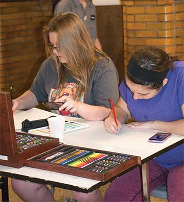 Sophomores Taylor Hill (left) and Andrea Davis work on drawings at one of several tables set up in the hallways where students produced sketches, paintings and designs. Event coordinator Jennifer McMillen said one-quarter of the district's students were involved in the evening, which also included choral and band performances.