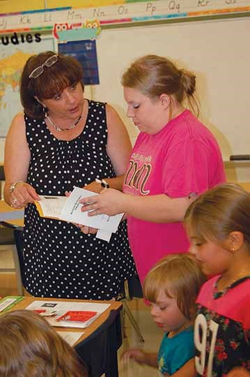 At the K-3 Campbell Elementary, second-grade teacher Jennifer Beek helps parent Kelli Johnson with some of the back-to-school paperwork. Principal Jill Imes said the event has helped ease some of the jitters for young students and answers questions for parents, avoiding confusion when classes begin.
