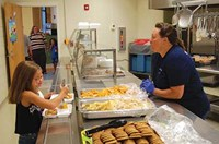 Campbell Elementary cafeteria staffer Ann Fenney kept busy serving up hot dogs, chips and cookies to returning students like Bryna Wellman (left) and Carly Fannin. After the orientation sessions, a mobile food truck with snow cones capped off the evening for youngsters and parents at both schools.