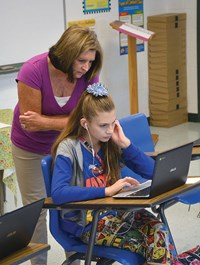 Bernie Carroll-Haney, a language arts teacher, observes seventh-grade student Lauren Souther as she works on a laptop.