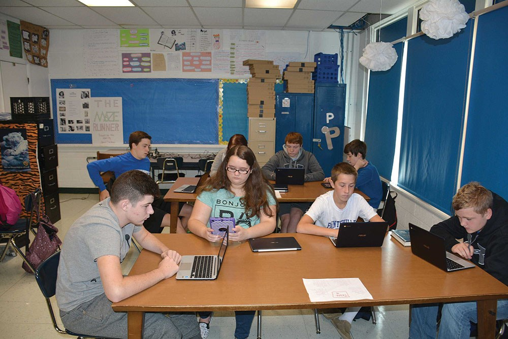 Students in Tiffany Burchett's eighth-grade English class work on reading assignments on digital devices. The students, in the foreground from l-r, are Gabe Stepp, Samarra Howell, Bryce Ward and Jay Wiley.