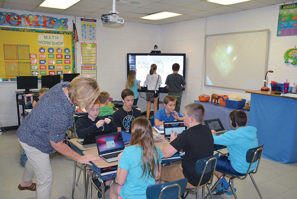 Students in Stephanie Tiller's fifth-grade math class use a Chromebook to work on assignments while other students do math problems on a MondoPad.