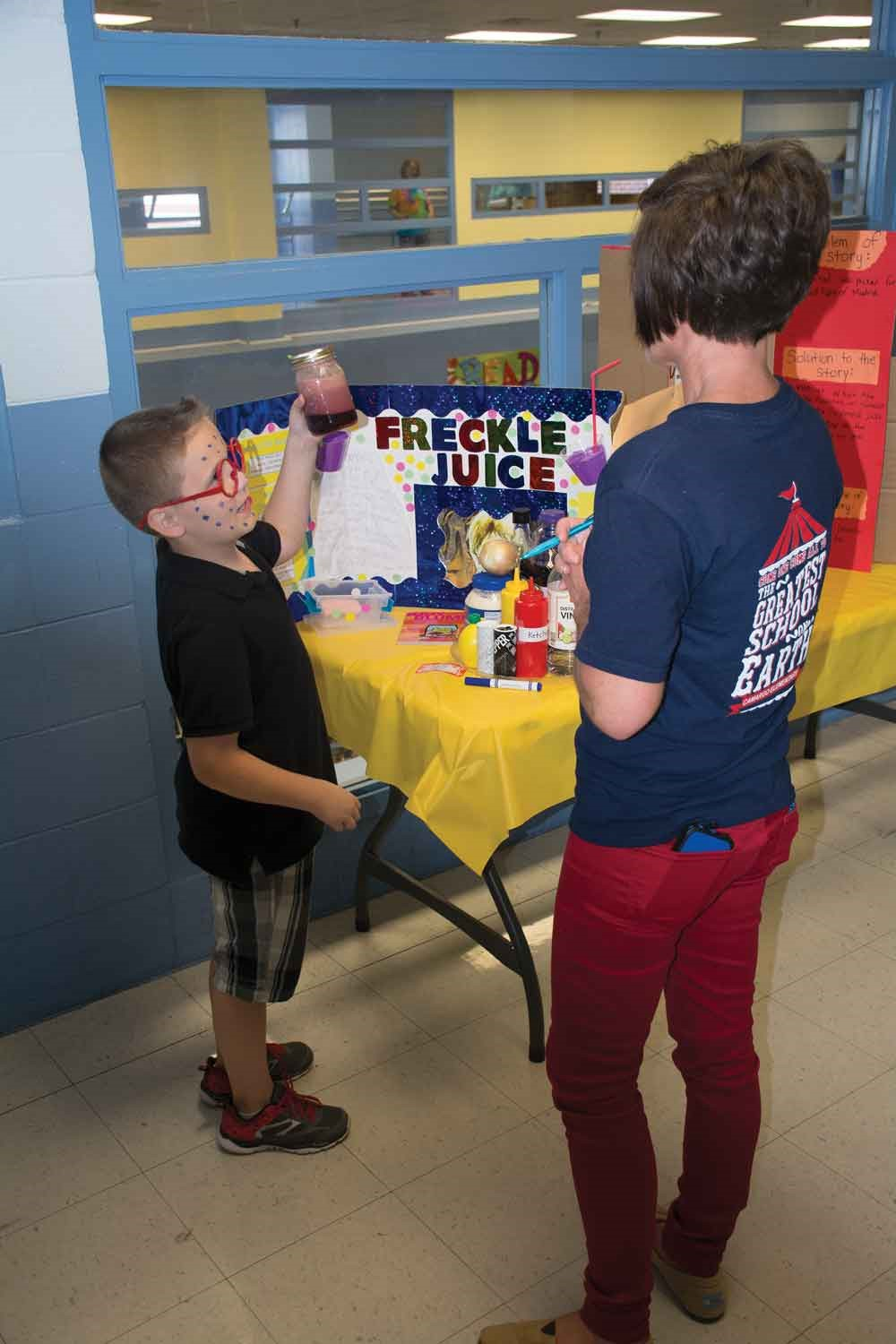 Projects were judged by several staff members, including the school's reading interventionist Tammy Jo White. Third-grade student Keegan Miller, who chose Freckle Juice for his project, shows White the homemade freckle juice he made for the event.