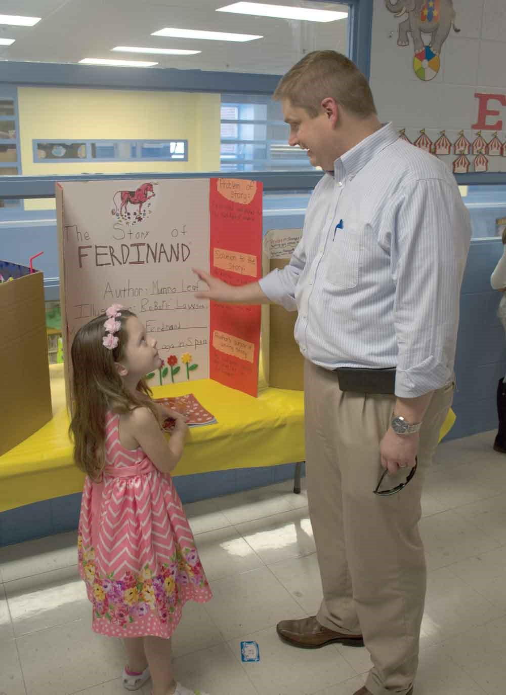 """Montgomery County Superintendent Dr. Matt Thompson talks with kindergarten student Aubrey Fossier about her book choice, The Story of Ferdinand. Thompson told her that was his favorite book. Fossier said it took her about three hours to do her project and that """"reading is my favorite thing in the world."""""""