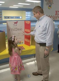 "Montgomery County Superintendent Dr. Matt Thompson talks with kindergarten student Aubrey Fossier about her book choice, The Story of Ferdinand. Thompson told her that was his favorite book. Fossier said it took her about three hours to do her project and that ""reading is my favorite thing in the world."""