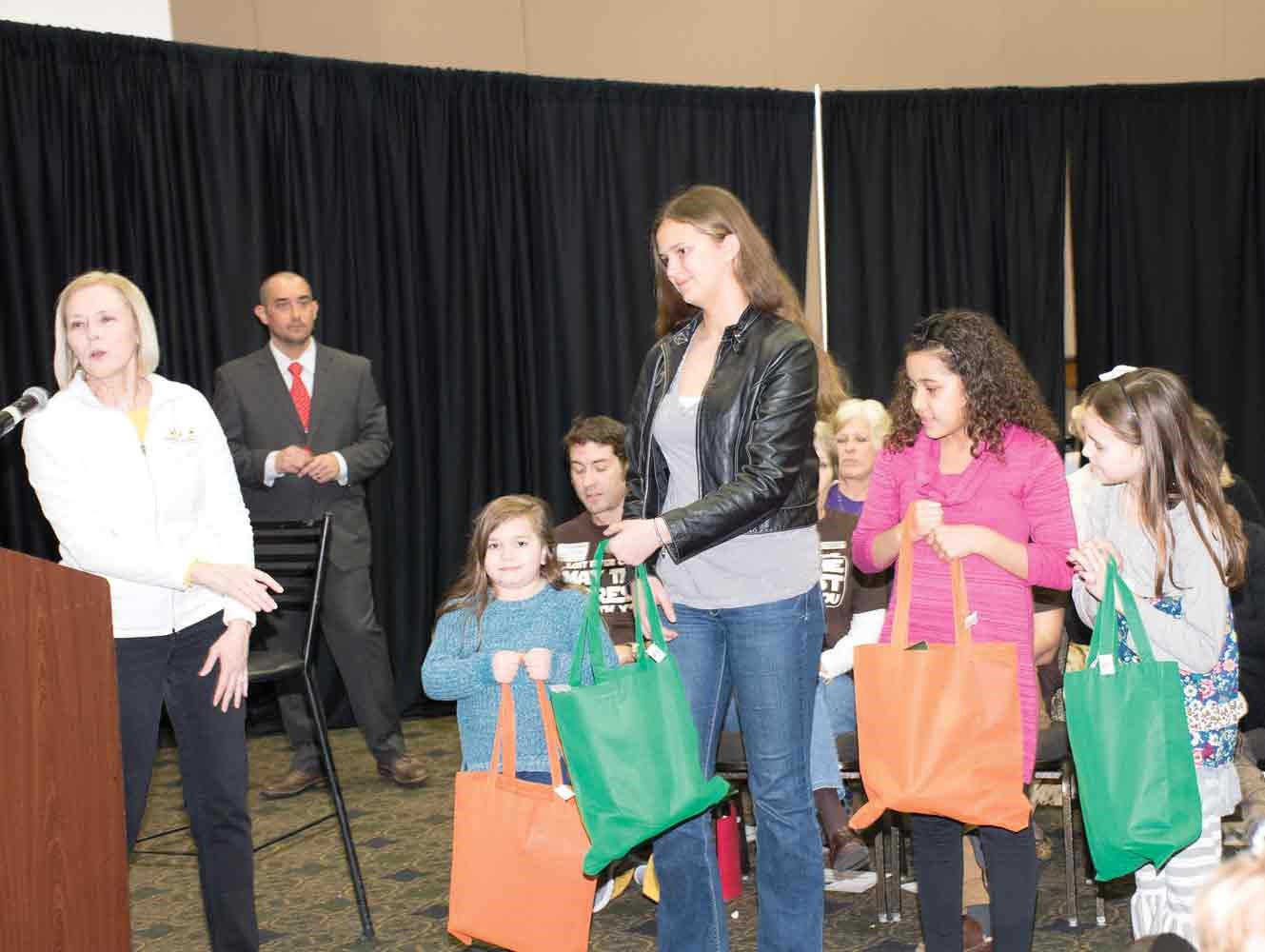 Community Education Director Debi Jordan recognizes four Warren County students for sweeping the event's arts program, in which they created designs for a local attraction's gift shop. From left, the students are Addison Rosado, a Jody Richards Elementary School first-grader; Liz DeMarse, a Drakes Creek Middle School eighth-grader; Harley Wilson, a Lost River Elementary School sixth-grader; and Hayden Wolf, a North Warren Elementary School third-grader. A fifth winner, Bosco Tuyisenge, a Henry F. Moss Middle School eighth-grader, was unable to attend.