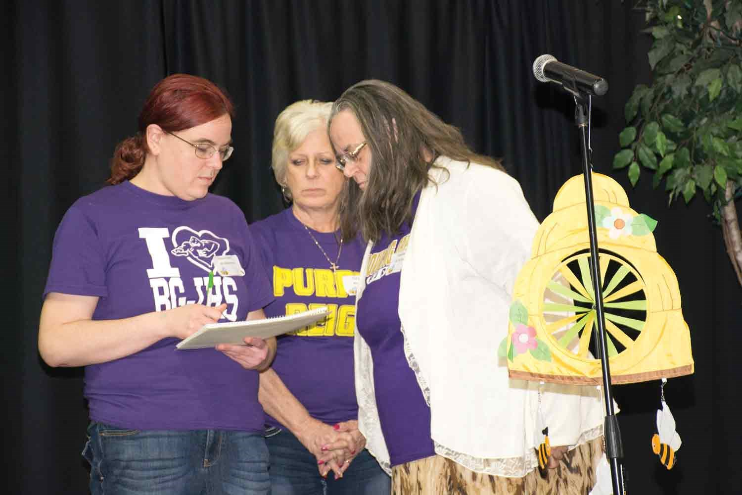 Members of the Bowling Green Independent-sponsored The Purple Powers that Bee team strain their brains before offering their response to the polysyllabic word quiz. In this year's event, 11 teams of three did most of the spelling, but in a trivia round, audience members were called on to take their best shot.