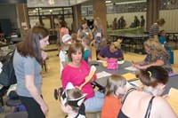 Spencer Elementary School secretary Judy Henry helps a mother complete enrollment paperwork for the 2016-17 year. Principals and other staff from both district elementary schools and its preschool program fielded questions from parents on topics like supplies and daily schedules.