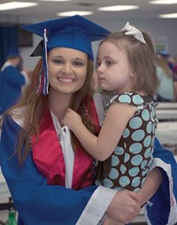 "The day began with a family breakfast in a packed Adair County High. Then, seniors such as Haley Cromwell  (pictured with little sister, Haven, a member of the Adair County kindergarten Class of 2017) quickly dressed in their caps and gowns to hit the road. Organizers also used the event to get everyone together for the official graduating class picture at the end of the traveling ""thank you"" show."