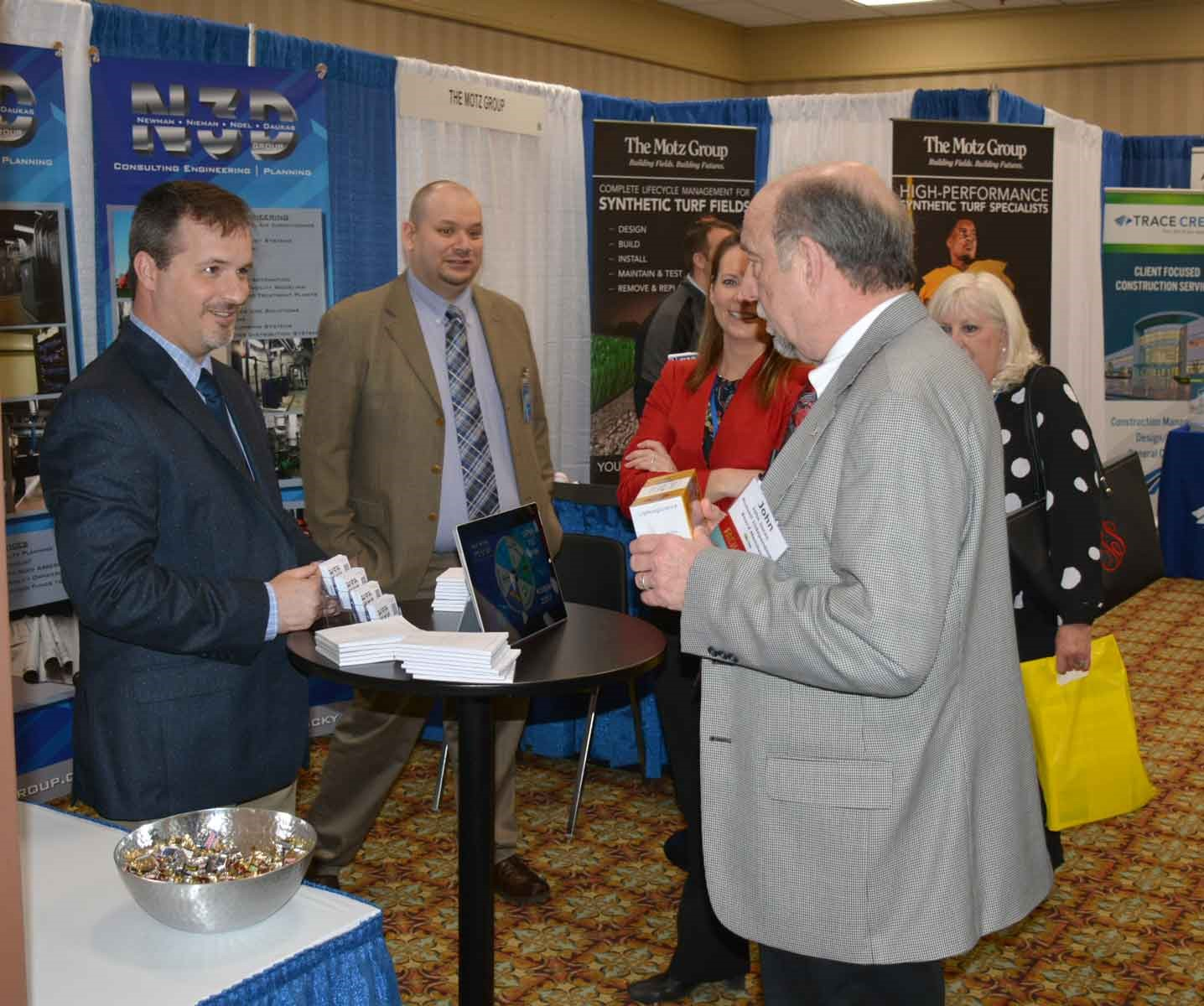 Russellville Independent board member INSERT NAME visits representatives of N3D Group Consulting Engineering and Planning of Lexington. More than 70 vendors had displays at the sold-out Trade Show.