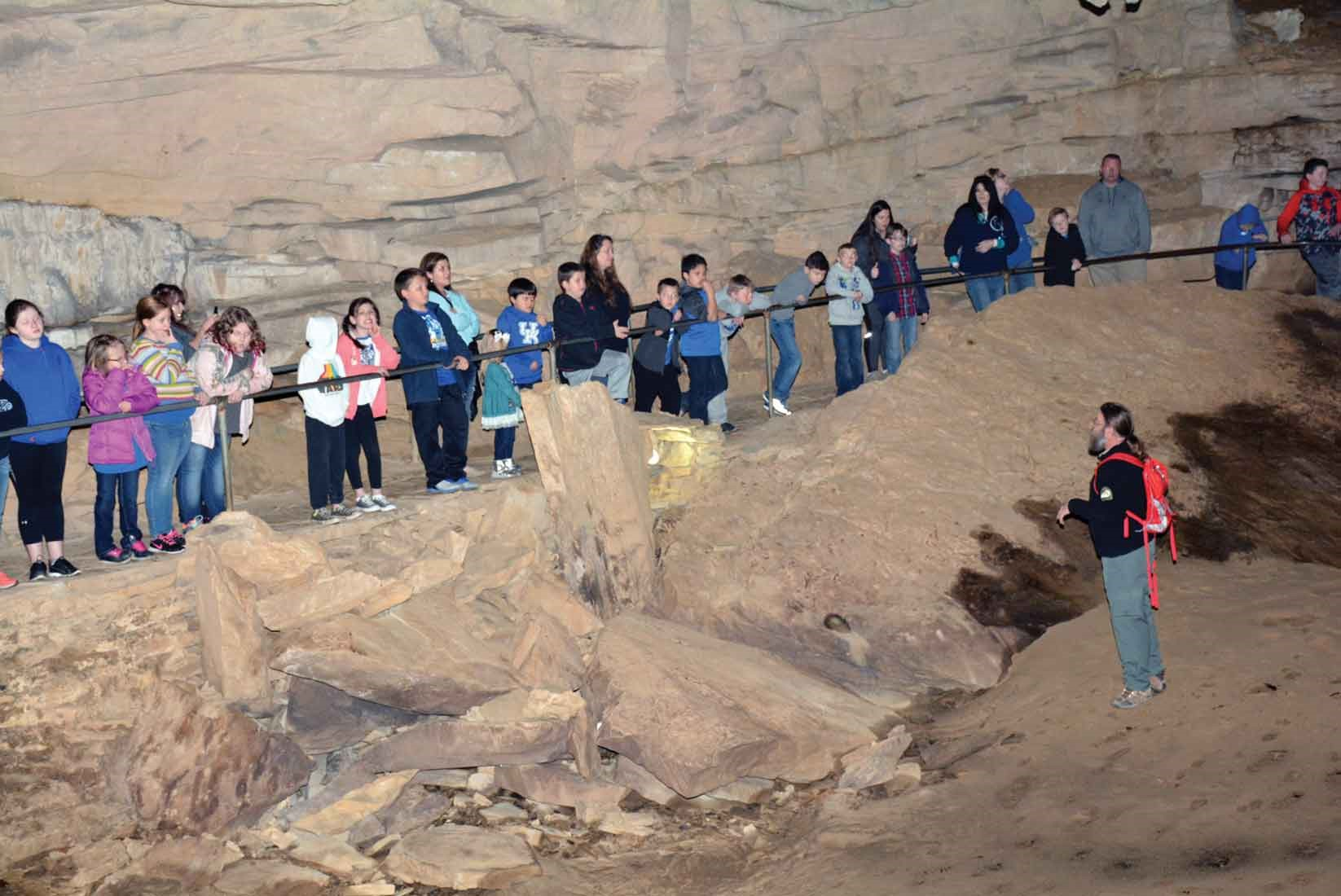 Park Adventure Ranger Coy Ainsley shows his tour group around Cascade Cave's Lake Room after a short walk from a cavern known as the Dance Hall, where a private owner of the caves used to stage weekly dances. Ainsley says the park may average 3,000–4,000 students on field trips each year.