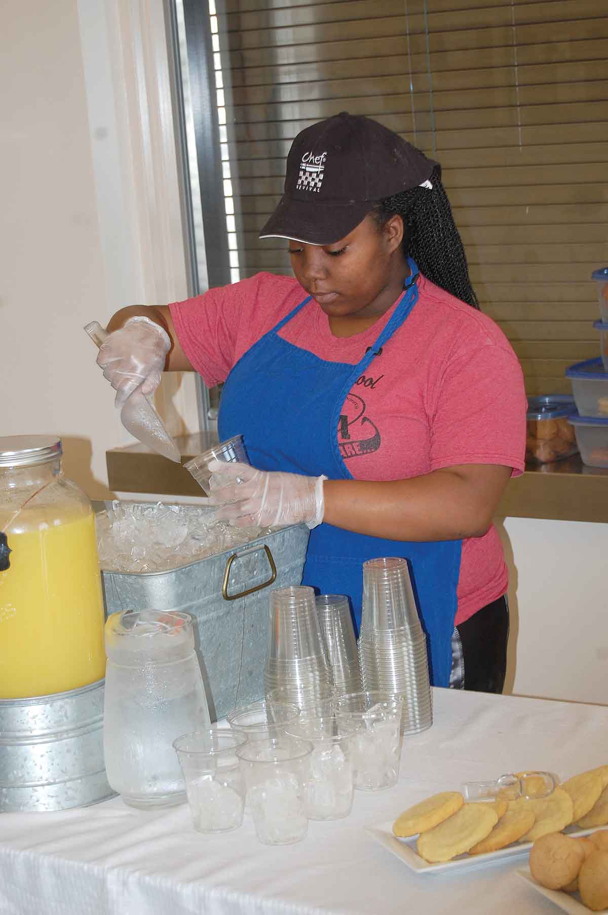 Diamond Beachamp, a culinary arts student, prepares drinks for the visitors' meal of buffalo chicken