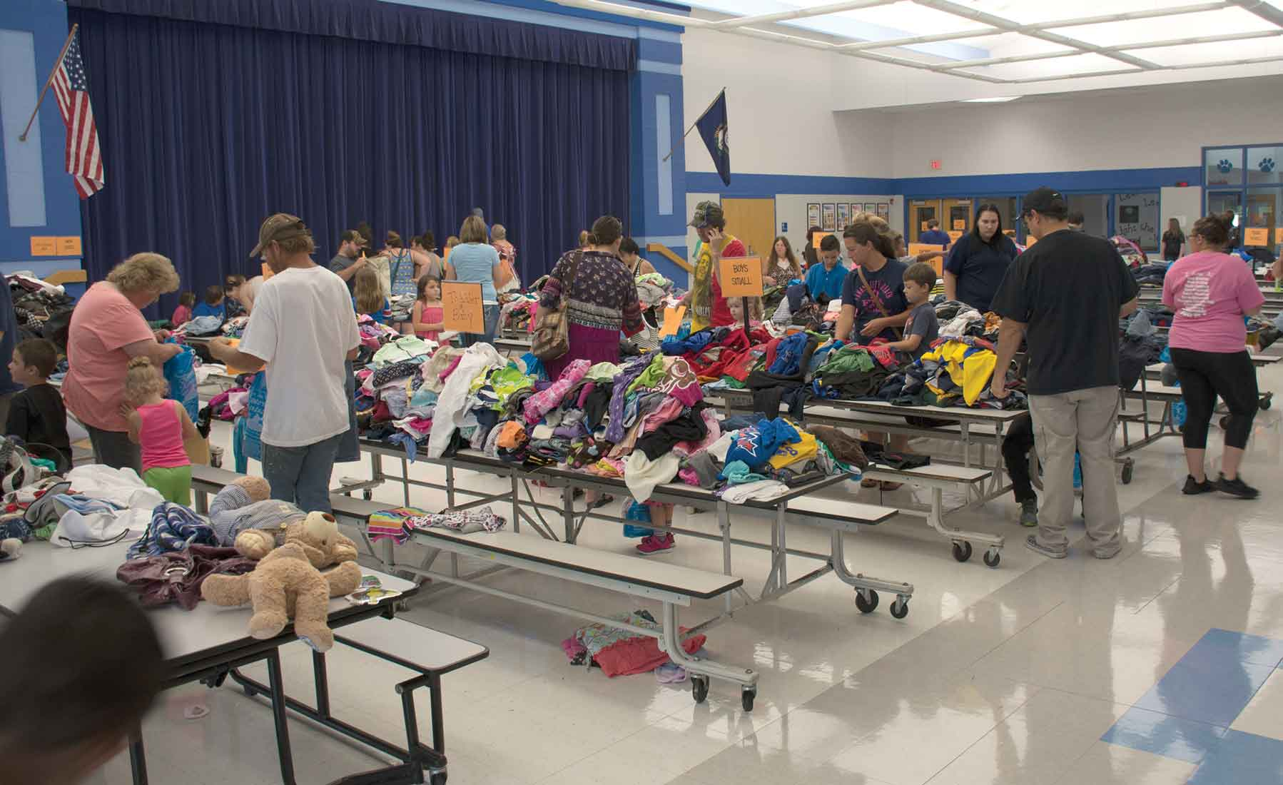 Parents and children look through tables loaded with donated clothing. Participants received a bag they could fill up during the fair. According to David Eddy, Trimble County's family resource coordinator,  almost 500 people attended this year's event.