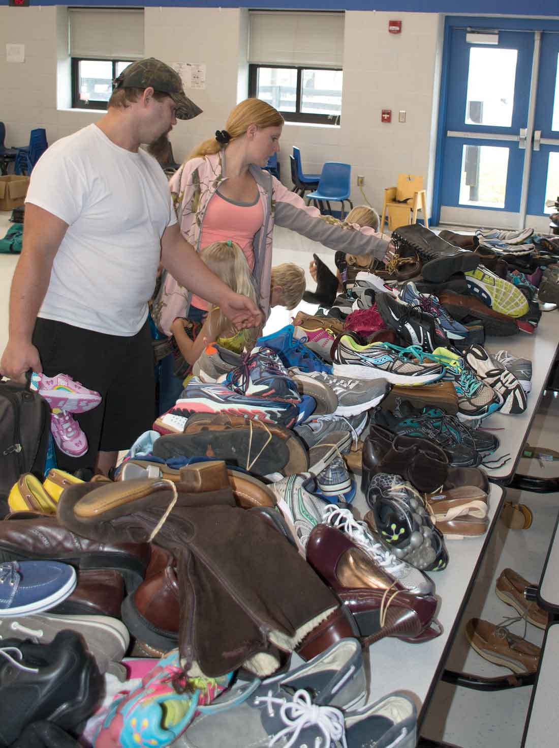 "Jeffrey and Amanda Tackett look at shoes with their three children. In addition to used shoes, each student who attended was given a card to receive a free pair of new shoes that had been donated by local churches through a ""Shoes in the Pews"" program."