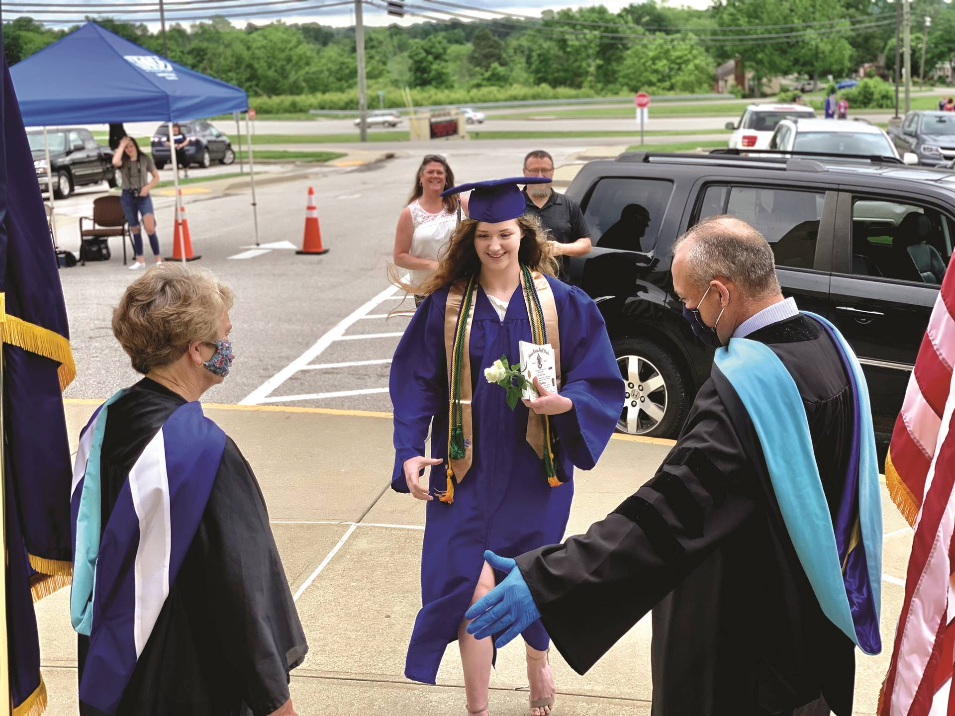Kenton County school board member Karen Collins and Superintendent Henry Webb welcome a graduate at