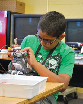 Karan Desai is deep in concentration in his Robotic Engineering course for middle grades. Using the Mind Storm robot program, students built a Lego robot and used computer software to program and direct it to do various tasks.
