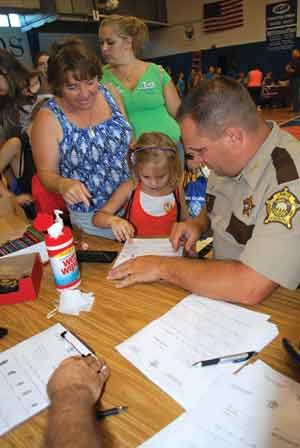 Lewis County Sheriff Johnny Bivens helps Tollesboro Elementary School third-grader Cheyenne Clark and her grandmother produce a set of fingerprints on a form designed to help law enforcement officers and families in case of an identification emergency.