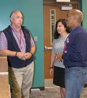 Charlie Bryant (left), facilities director for Anchorage Independent Schools, talks with Superintendent Kelley Ransdell and Principal Andrew Terry. All three said educating students and staff about the importance of energy savings has made a difference.