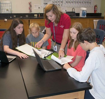 Anchorage students talk to teacher Raechel Minor. The students are members of the school's STEM Club, which made energy awareness its focus last school year..