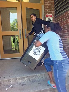 Students at Morton Middle School return a recycling bin to a classroom after emptying it into an outside receptacle.