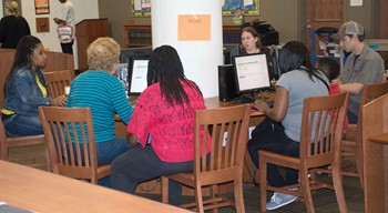 Parents register their children for school at the kindergarten registration event at Christian County Middle School in April. This is the second year that the district has used online registration.
