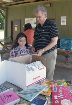 Caverna Independent school board Chairman Wayne Hatcher helps his granddaughter Rebecca Piercy sort through the reading possibilities at the Horse Cave City Park, where the district set up its mobile summer reading program.
