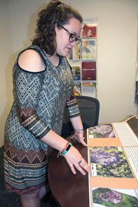 Rebekah Vermillion looks over a poster with aerial drone photos of an archeological site in Mexico.