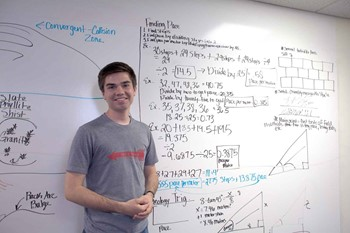 Zeb Hart in front of a dry erase board where students have worked on some calculations.