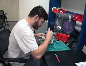 Garrett Jones works to construct a drone using parts he made from a 3-D printer.