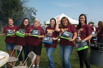 A group from Elkhorn Middle School poses with their giveaway Franklin County Schools lunch containers at the district's opening day cookout.