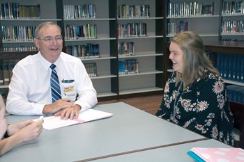School safety assessment team member Mike Blevins, a retired Boone County Schools administrator, shares a lighter moment with a group of Nelson County High school students he is interviewing, including Katye Berry.