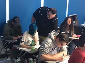 Math teacher Dustin Adams helps out a student in one of his classes at Paintsville High School, from which he graduated in 2012. (Photo courtesy of Paintsville Independent Schools)