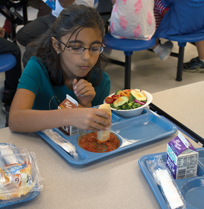 Tolliver Intermediate student Mahi Patel enjoys the freshly made marinara sauce and a salad topped with peppers and tomatoes from Overman's Bluegrass Fruits and Vegetables.