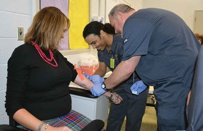 Bowling Green High School Medical Arts Academy student Jerico Howard, center, prepares to draw blood from school administrator Elisa Brown, with a little guidance from instructor Matthew Atkinson.