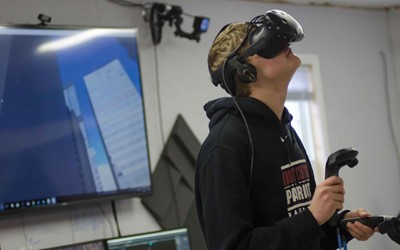 Knott Central student Colbie Napier tests the new virtual reality program at the Kentucky Valley Educational Co-op. What he is seeing through the headset is displayed on the screen behind him. KVEC is adding a VR program as another option for students.